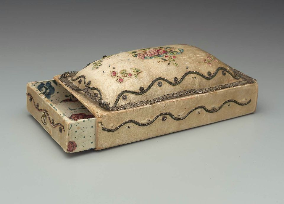 Embroidered 18th century pincushion sewing box, foundation of cardboard box with sliding drawers at each end, ends of drawers, box sides & attached pincushion of white satin (now yellowed), gold metal thread & sequins on sides, bottom & interior of box and drawers covered with block printed paper. Museum of Fine Arts, Boston