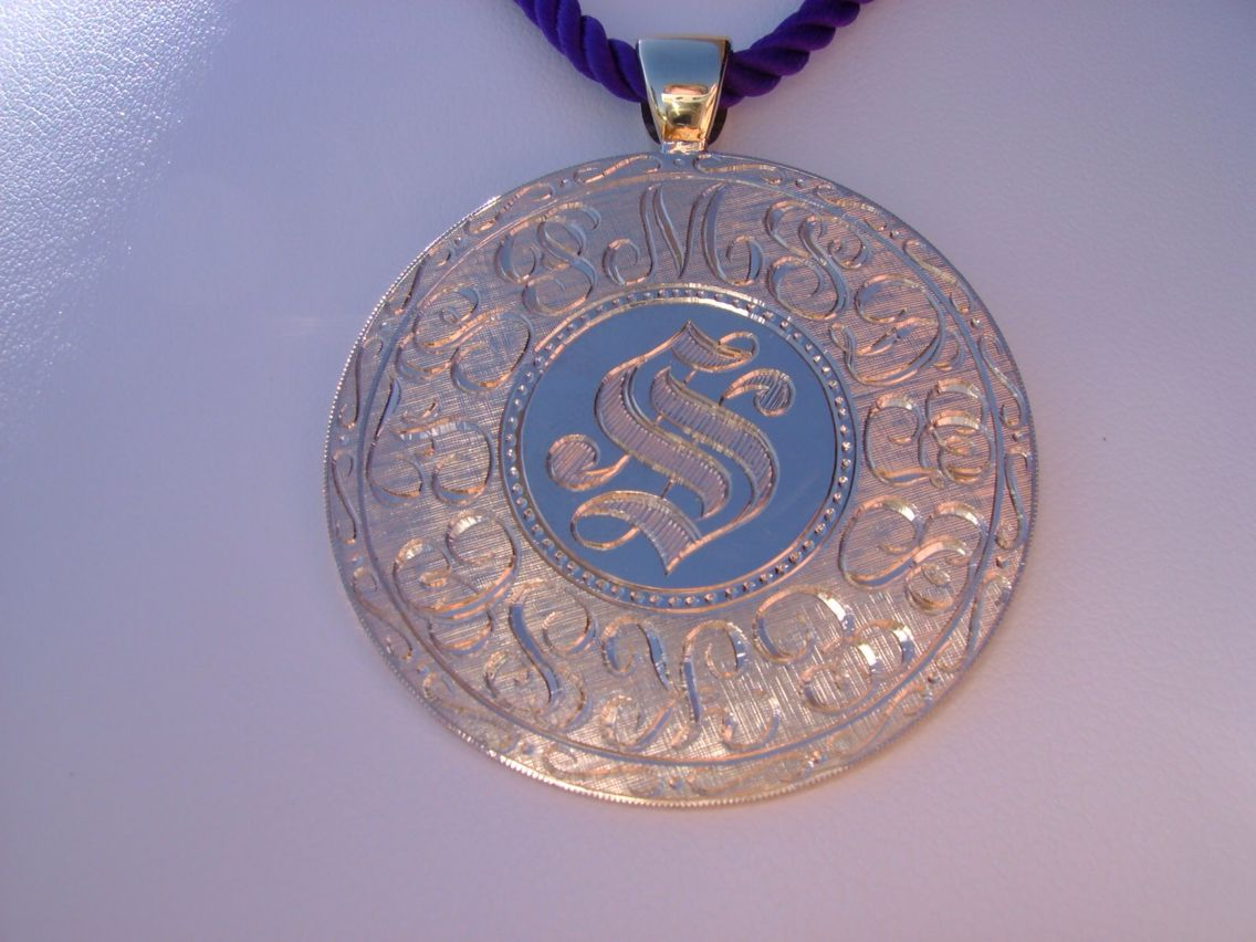 This is an example of Richard Neustaedter's, Generational Pendant.  For this piece, the last name initial is an S.  The S is done in an Old English style to reflect the owners taste for tradition.  The lettering surrounding the S is the initials of all of her children.  Notice how the surrounding initials almost look like lace-work or filigree.  This is a true heirloom piece with the whole family represented, and will be passed from generation to generation.