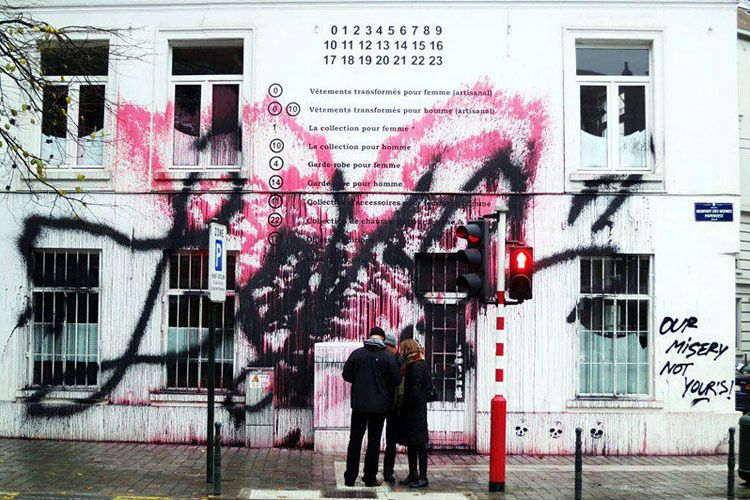 """The Maison Martin Margiela store in Brussels is the latest to be vandalized—oh sorry, tagged—by Kidult, the graffito who's previously defaced Hermès, Kenzo, Christian Louboutin, and Marc Jacobs. Across the facade is written, in cursive, the word """"Love"""" in black spray paint, on top of what looks like a face in pink. Rather mysteriously, in the lower right corner he 's also written """"OUR MISERY NOT YOUR'S!"""" Kidult has stated before he targets houses that use graffiti in their designs (which is…"""