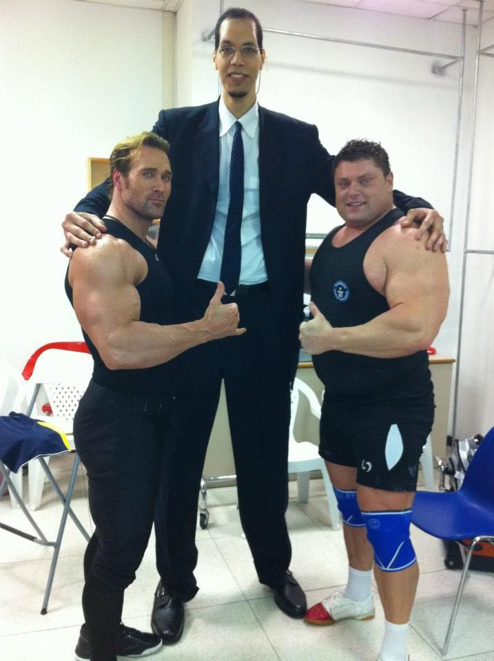8 ft tall man next to two 6 ft 3 bodybuilders
