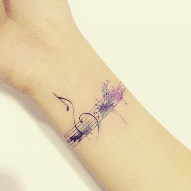 tatouage de femme : tatouage notes de musique aquarelle sur poignet