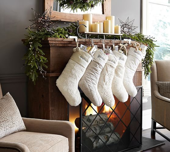 Carolers Displayed On A Mantle With Garland And Stockings: Mantle Sleigh Stocking Holder