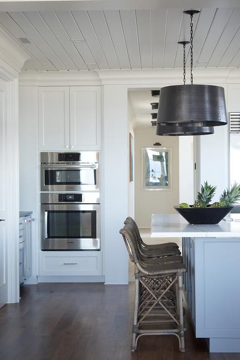 Well Designed White Kitchen Features Rattan Counter Stools Placed In Front Of A Gray Wainscoted