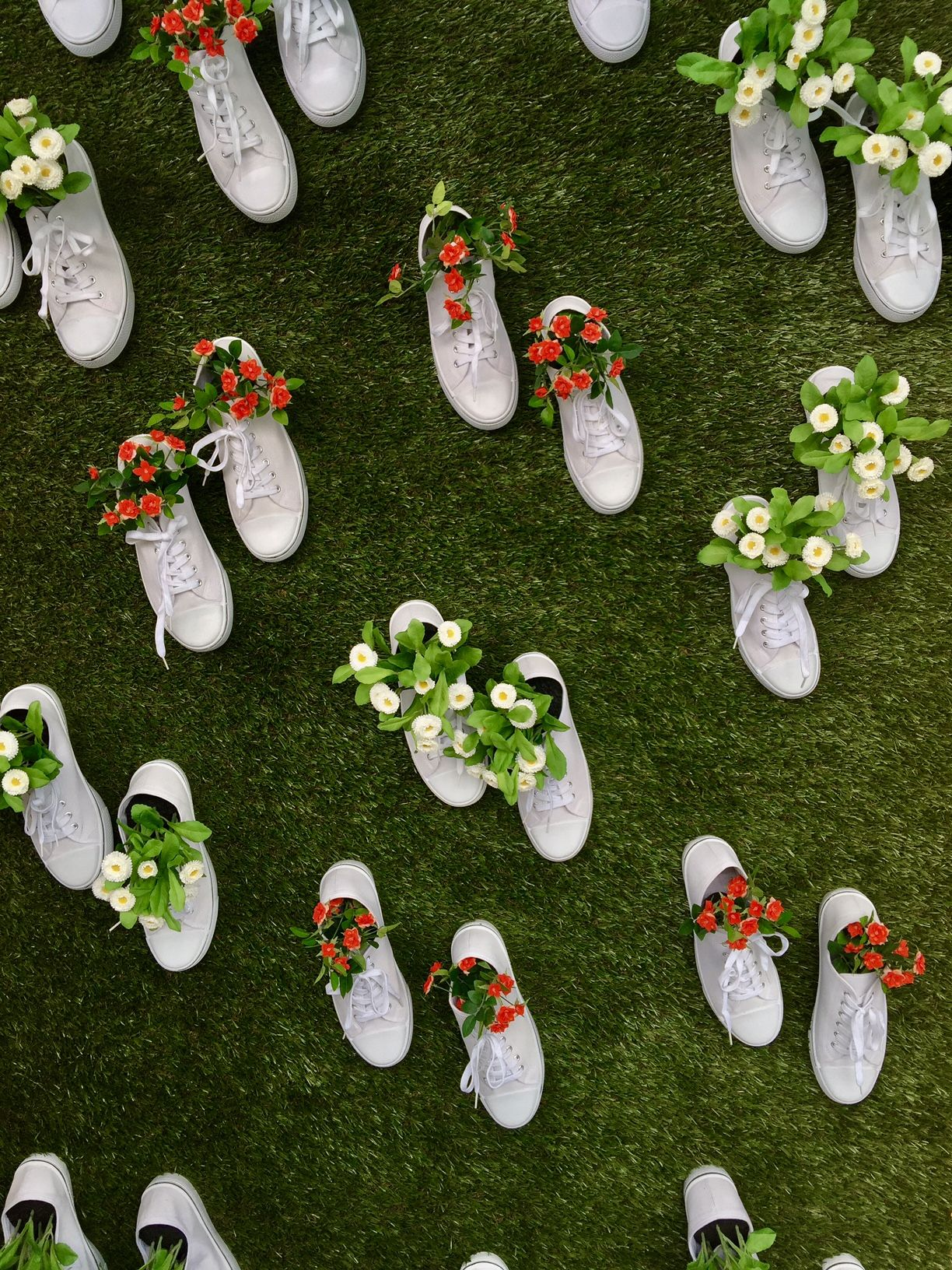 Tennis shoes attached to the wall and used as vases for