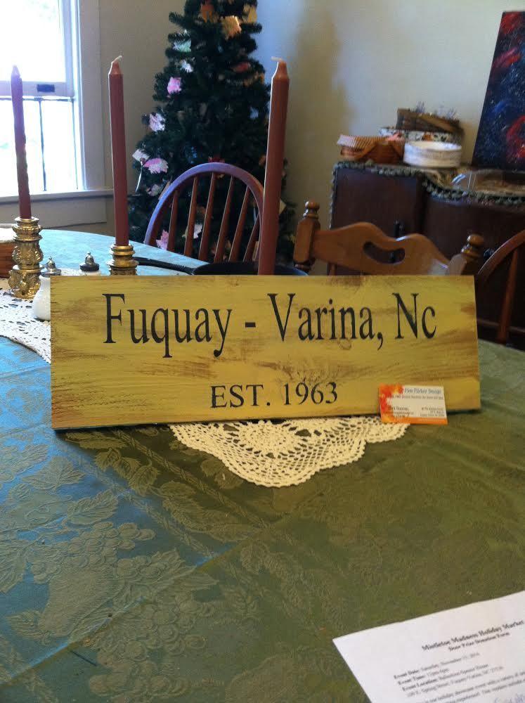 Sara Duncan with Flea Flicker Designs donating Fuquay-Varina sign for Mistletoe Madness holiday market