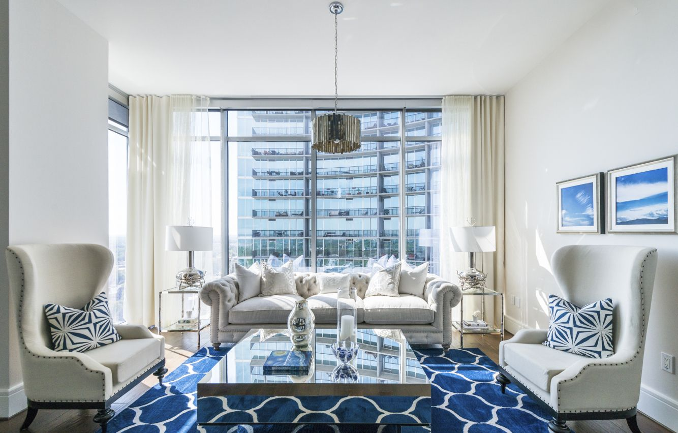 Modern condo with blue decor  Large window modern fixtures living room upholstered furniture luxury decor design city living urban condo condominium views area rug rugs glass table lamps