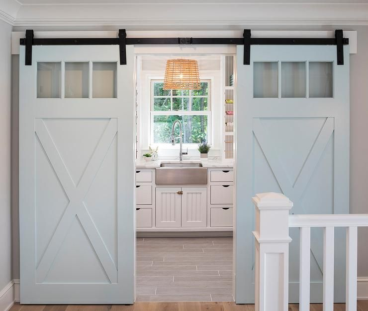 Light Blue Barn Doors On Rails Open To White And Gray Craft Room Fitted With Gray Staggered Flo Lake House Interior Luxury Interior Design Home Interior Design