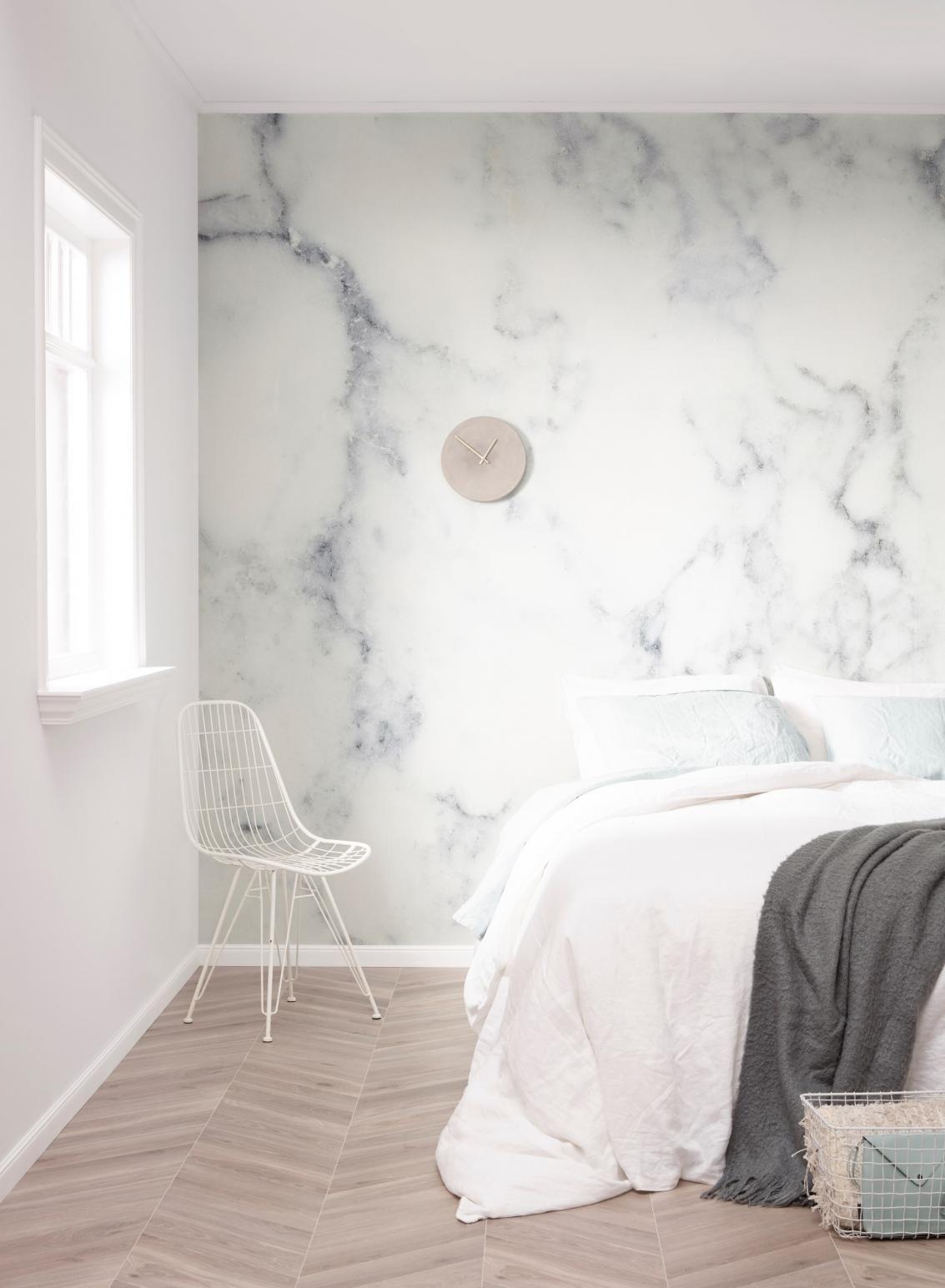 Een rustige slaapkamer met een licht marmer behang
