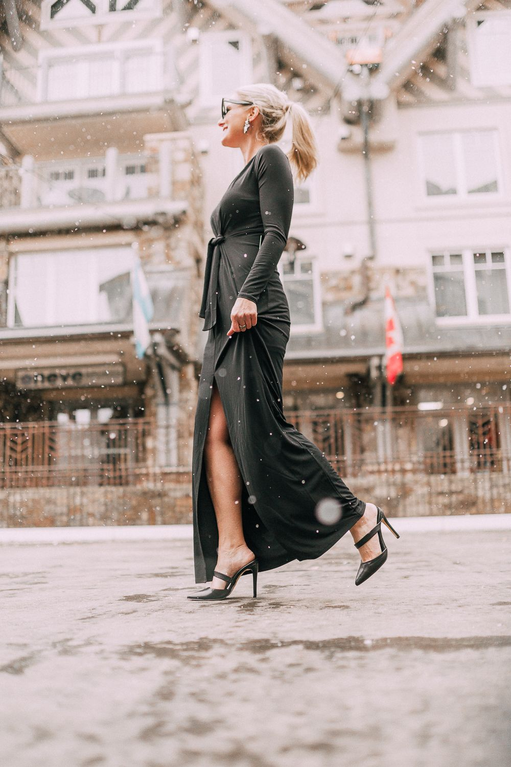 d955cfc78553 Unexpected holiday party outfits featuring a long black maxi dress with high  slit to show off legs and a knot under the bust on blonde fashion blogger  in ...