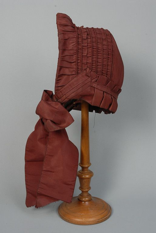 597 BURGUNDY SILK DRAWN BONNET, MID 19th C Seven channels of reed or wire, box pleats at neck, height 9 width 8 inches. Excellent. $57.50