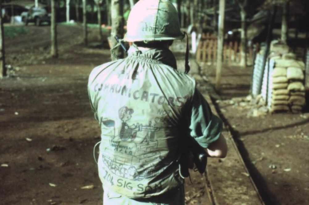 Australian soldier of the 104 Signal Squadron shows off the artwork on his flak jacket, 1969.