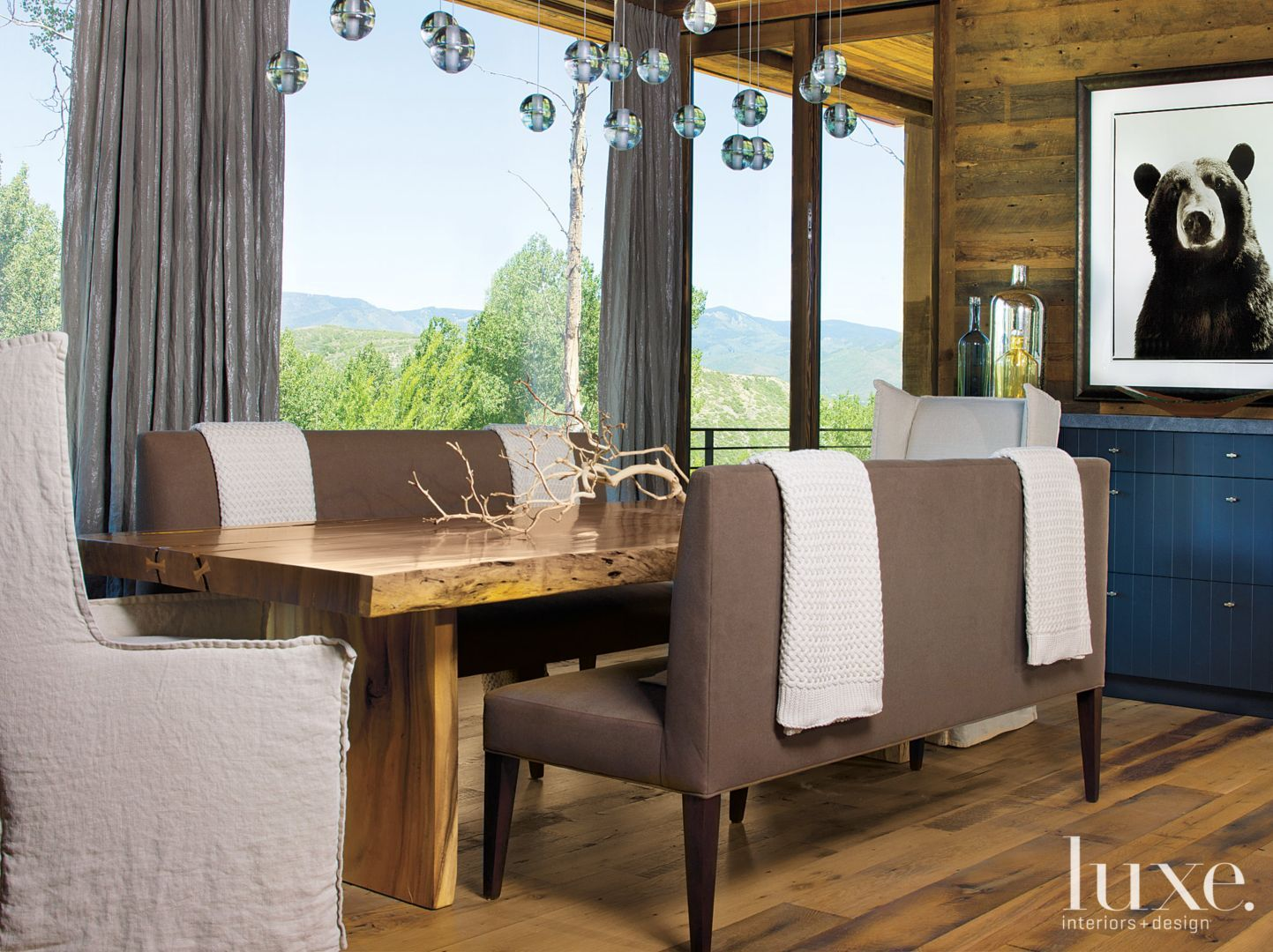 This narrow solid wood dining table adds warmth and a bit of rustic charm to a modern dining room.