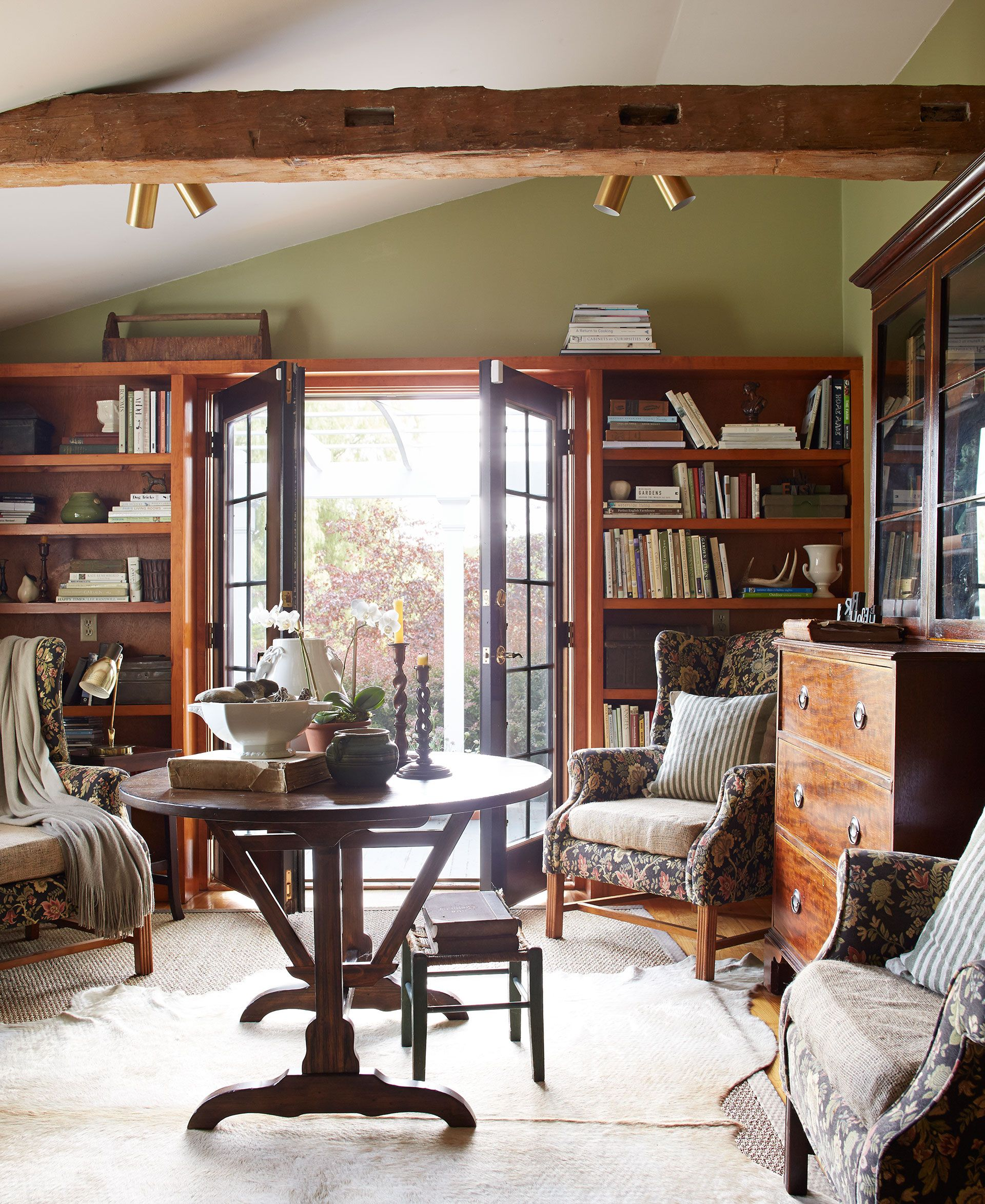 In the library, mismatched wingback chairs are unified with floral brocade upholstery and burlap cushions.