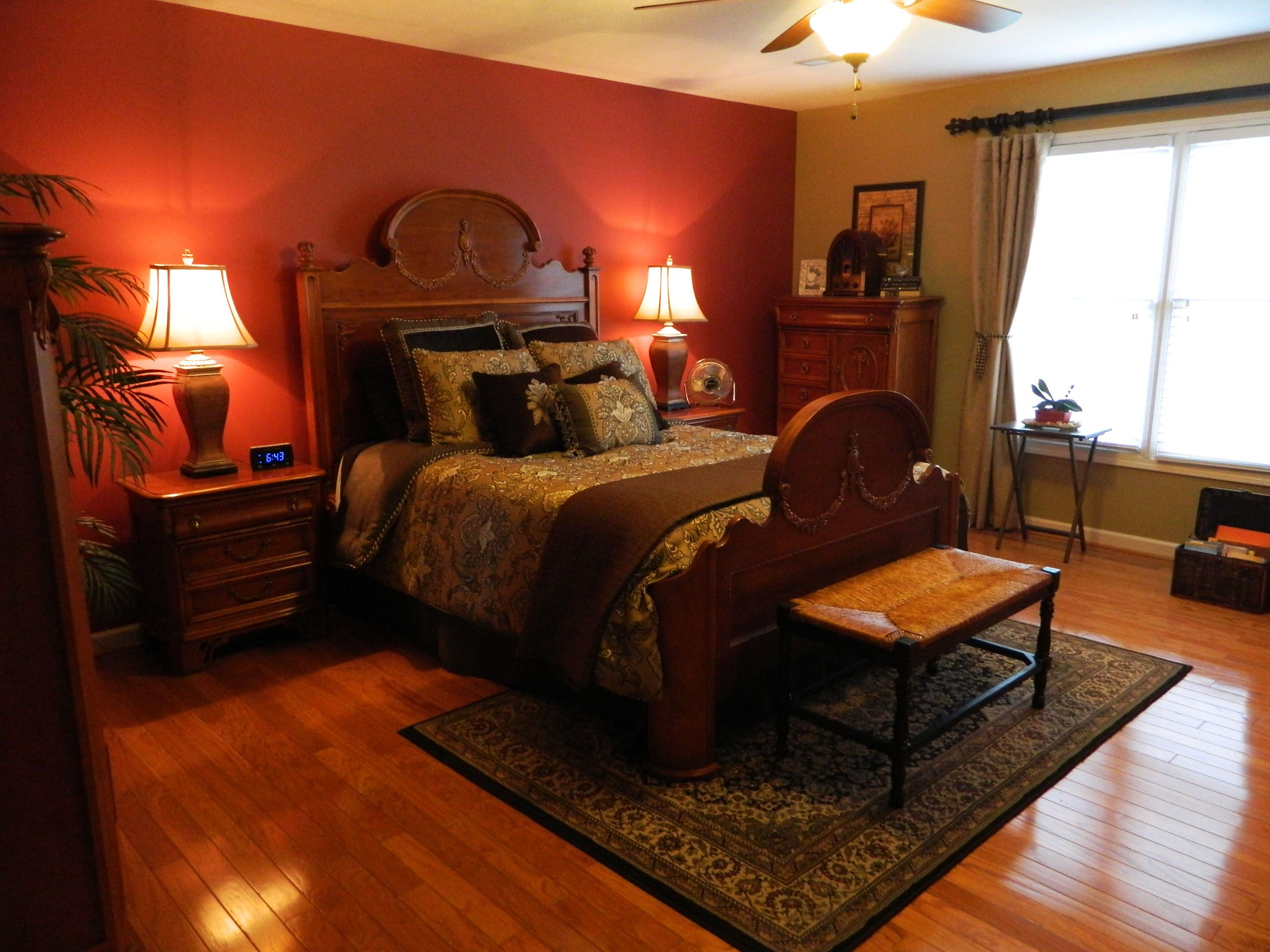 Master bedroom wall painted brick red. French country