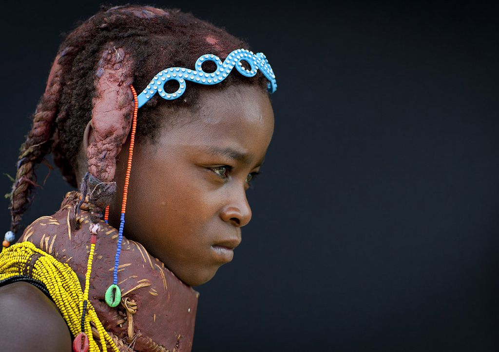 Mwila Girl With The Traditional Vikeka Mud Necklace, Angola  . Each period of their lives corresponds to a specific type of necklace. When they are young, girls wear heavy red necklaces, made with beads covered with a mix of soil and latex. Later , girls wear a set of yellow necklaces called 'Vikeka', made of wicker covered with earth. Once married they start to wear a set of stacked up bead necklaces, called 'Vilanda'. Women never take their necklace off . Huila , Angola