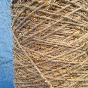 A dense Jute yarn with a contempary twist! Gold yarn twisted around with gold tinsel and gold 'brushes' intermittently spaced. Also availab...
