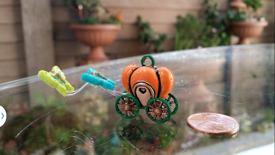 DIY Fairy Garden Pumpkin carriage pulled by two beautiful butterflies.  The carriage is a small metal locket that was painted to bring out the detail.  The reins are jewelry wire and the butterflies are plastic beads.