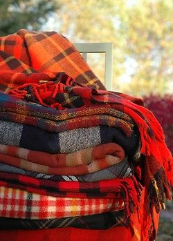 a pile of plaid blankets
