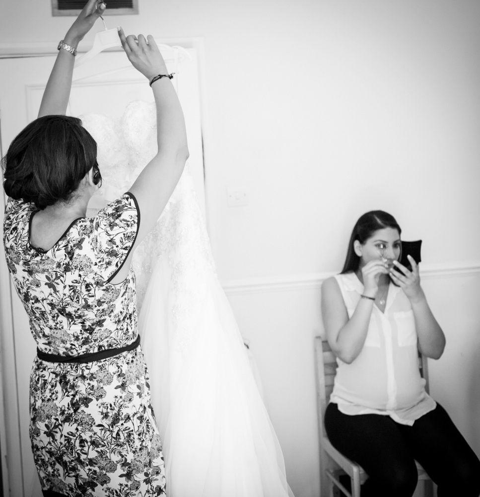 Brides sister hanging her wedding dress, whilst bride does her eyelashes