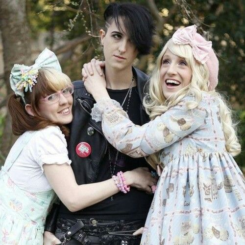 Lovely Lor and a Lolita friend hugging a Visual Kei friend.