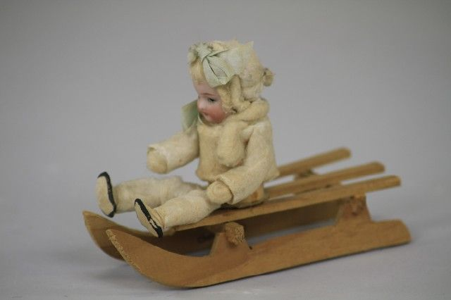 Lot # : 1453 - BISQUE HEAD BABY ON WOOD SLED CANDY CONTAINER