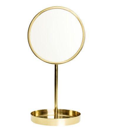 Kulta. Pieni pöytäpeili lasia, kehys ja jalka metallia. Pyöreä, alapuolelta pehmustettu jalka. Peilin halkaisija 12 cm, korkeus 26 cm.