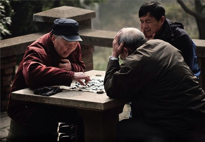 Two old men engage in a game of go while another looks on.