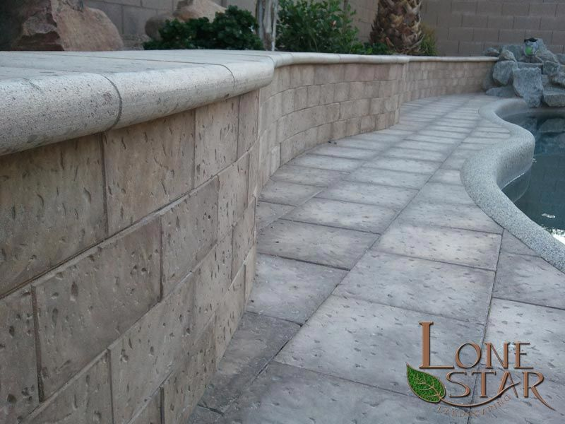 artistic pavers on retaining wall and around swimming pool in