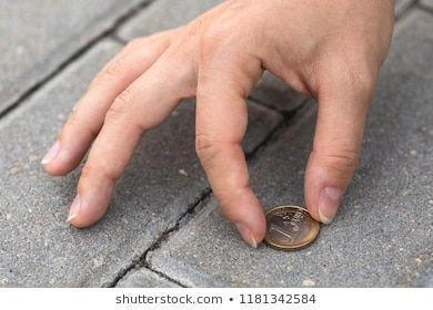 Lost and found money Female hand picking one euro coin from the ground
