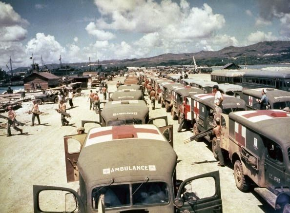 View of military ambulances lined up on shore at Guam ...