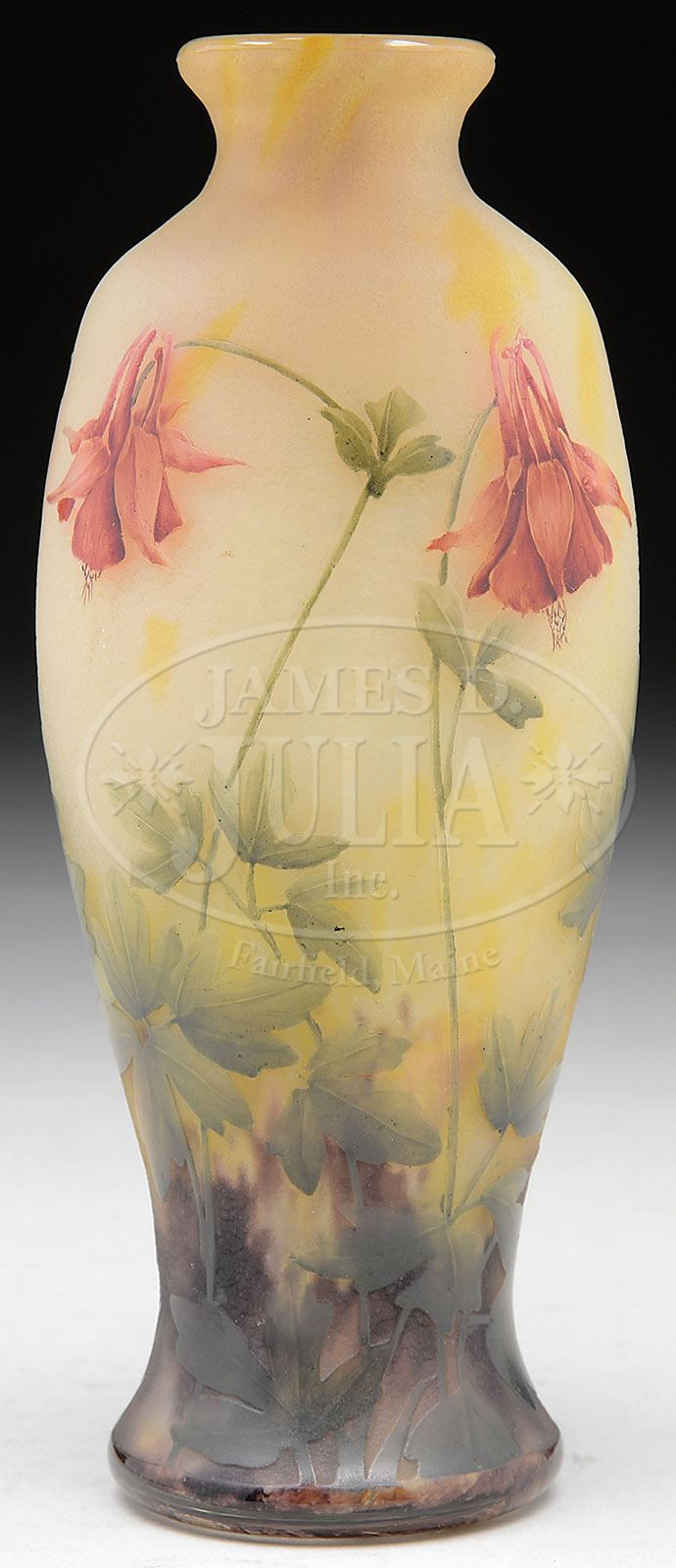James D. Julia, Inc. - Daum Columbine Vase. Daum vase isdecorated with cameo Columbine flowers, stems and leaves against a lightly mottled creamy yellow background that shades to mottled brown at the bottom. Each of the flowers is beautifully enameledwith shades o green in the leaves and stems and lovely reds and oinks in the flowers