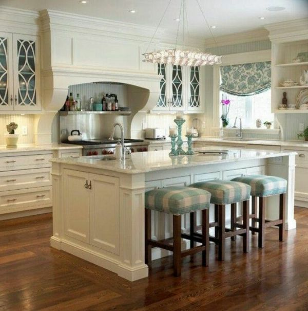 Kochinsel mit eingebauter Spüle und drei Barstühle für eine weiße