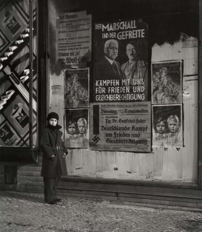 """Vishniac's daughter Mara posing in front of an election poster for Hindenburg and Hitler that reads """"The Marshal and the Corporal: Fight with Us for Peace and Equal Rights,"""" Wilmersdorf, Berlin. 1933 