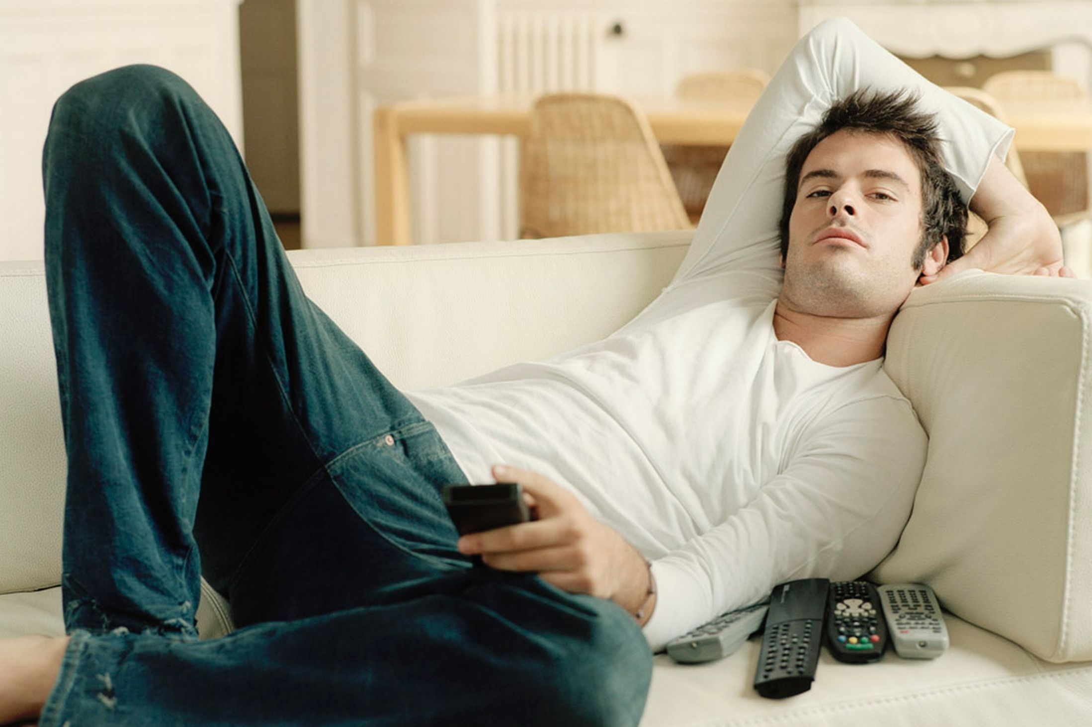 Man relaxing on sofa holding remote controls (2197×1463 ...