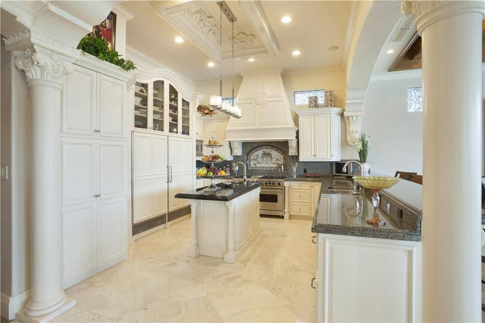 Thoroughly white kitchen features marble flooring with ornate ...