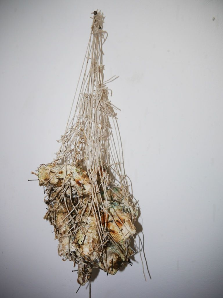 Plaster sculpture, corroded in 'liquid dementia', strung in netting by Christopher Holdsworth.