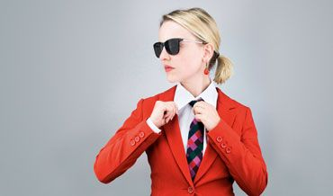 Kompetent in eigener Sache - Finanzstrategien für Frauen - Zu sehen ist eine junge Frau mit Sonnenbrille, bekleidet mit einem rotem Blazer, weißer Bluse und Krawatte.