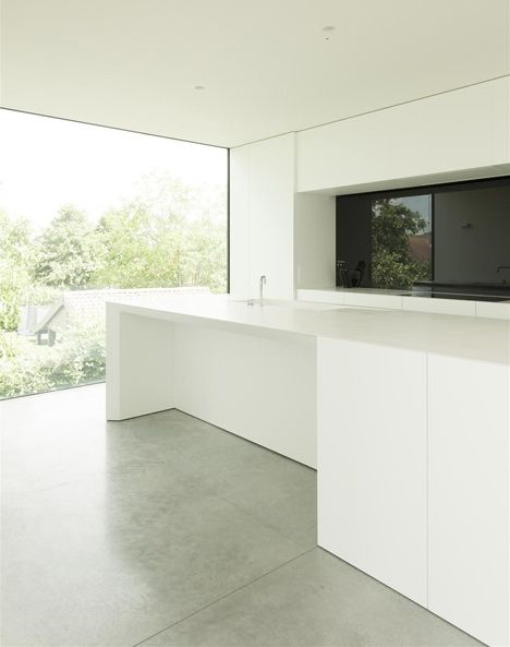 White kitchen with concrete floor and minimal window frames. House ...