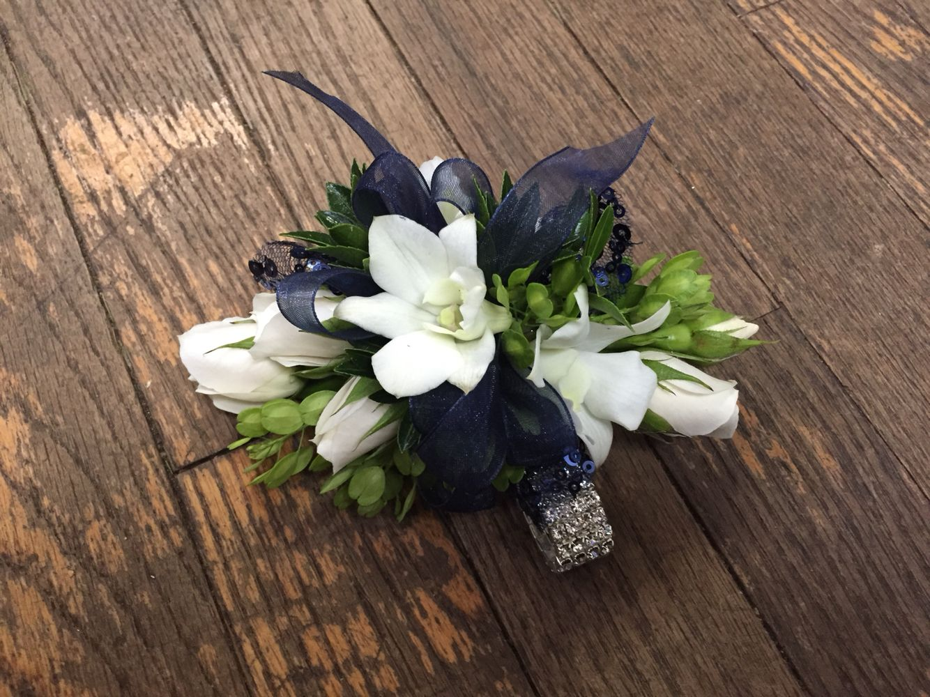 Navy blue and white prom corsage with roses and dendrobium orchids