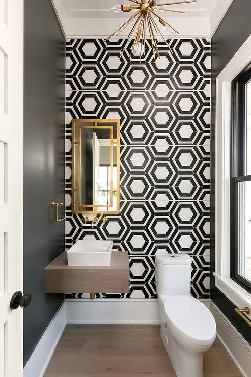 Black and white geometric tiles bring a bold accent to a powder room wall transforming a simple space into a mosaic masterpiece. #modernpowderrooms