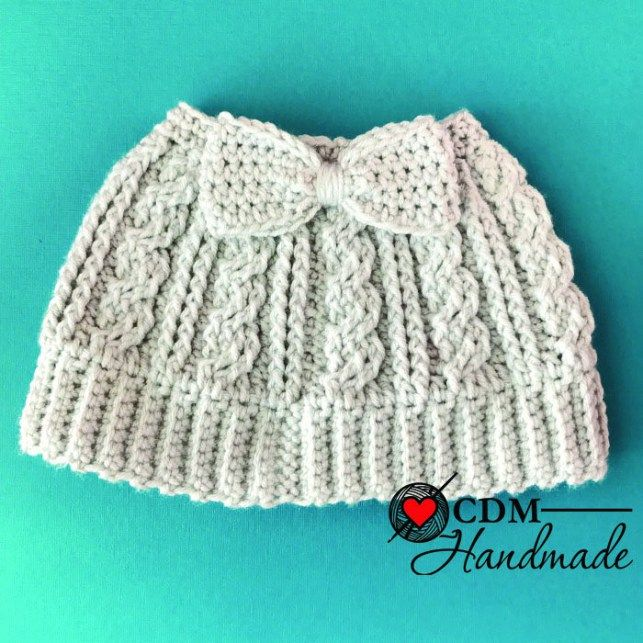 A free crochet pattern for a cabled messy bun bow hat. This is an intermediate skill pattern but the result is just elegant.