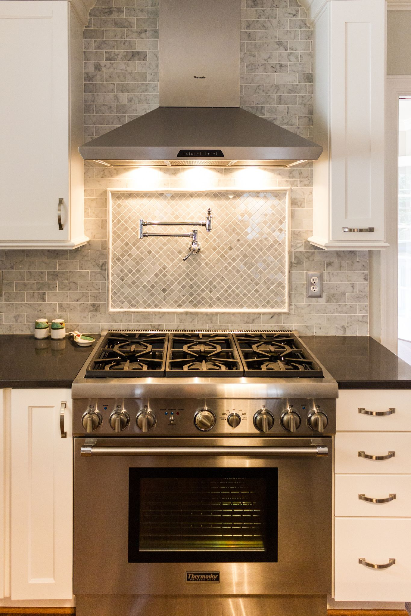 white kitchen with marble subway tile and tile backsplash over stove on Remodelaholic NEED POT FILLER