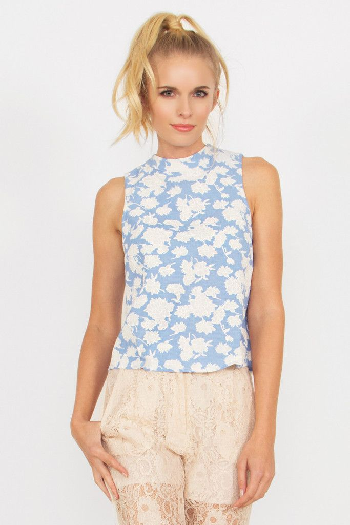 Sky blue floral top with a mock neck. Features a unique layered detail in the back.