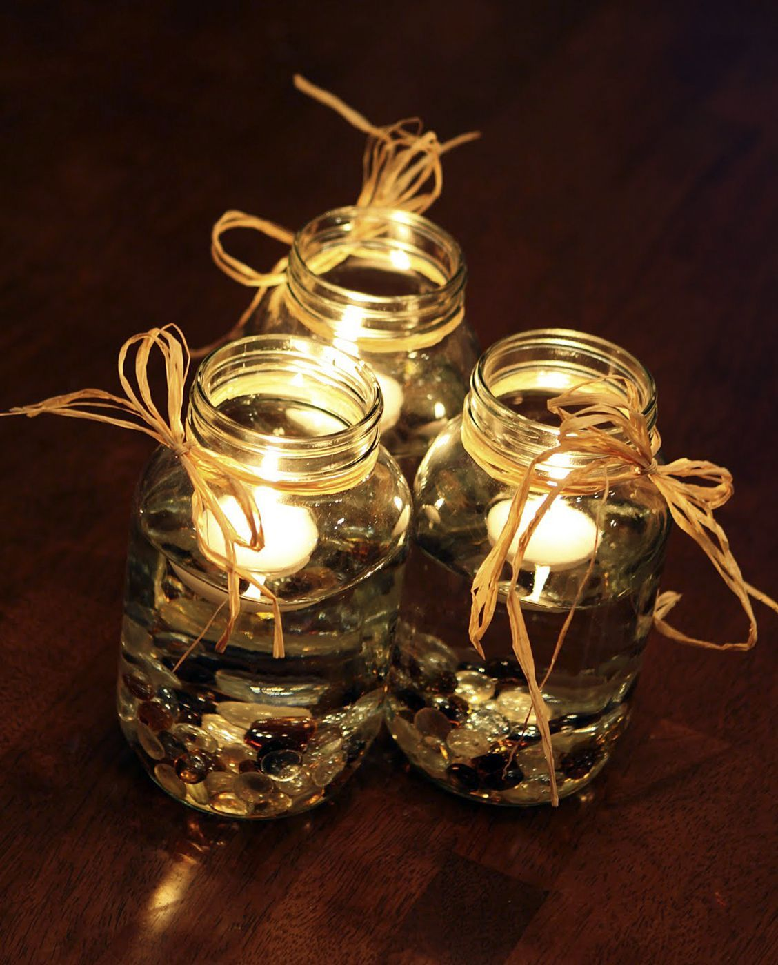 mason jars with raffia ribbon and rocks decorating with floating
