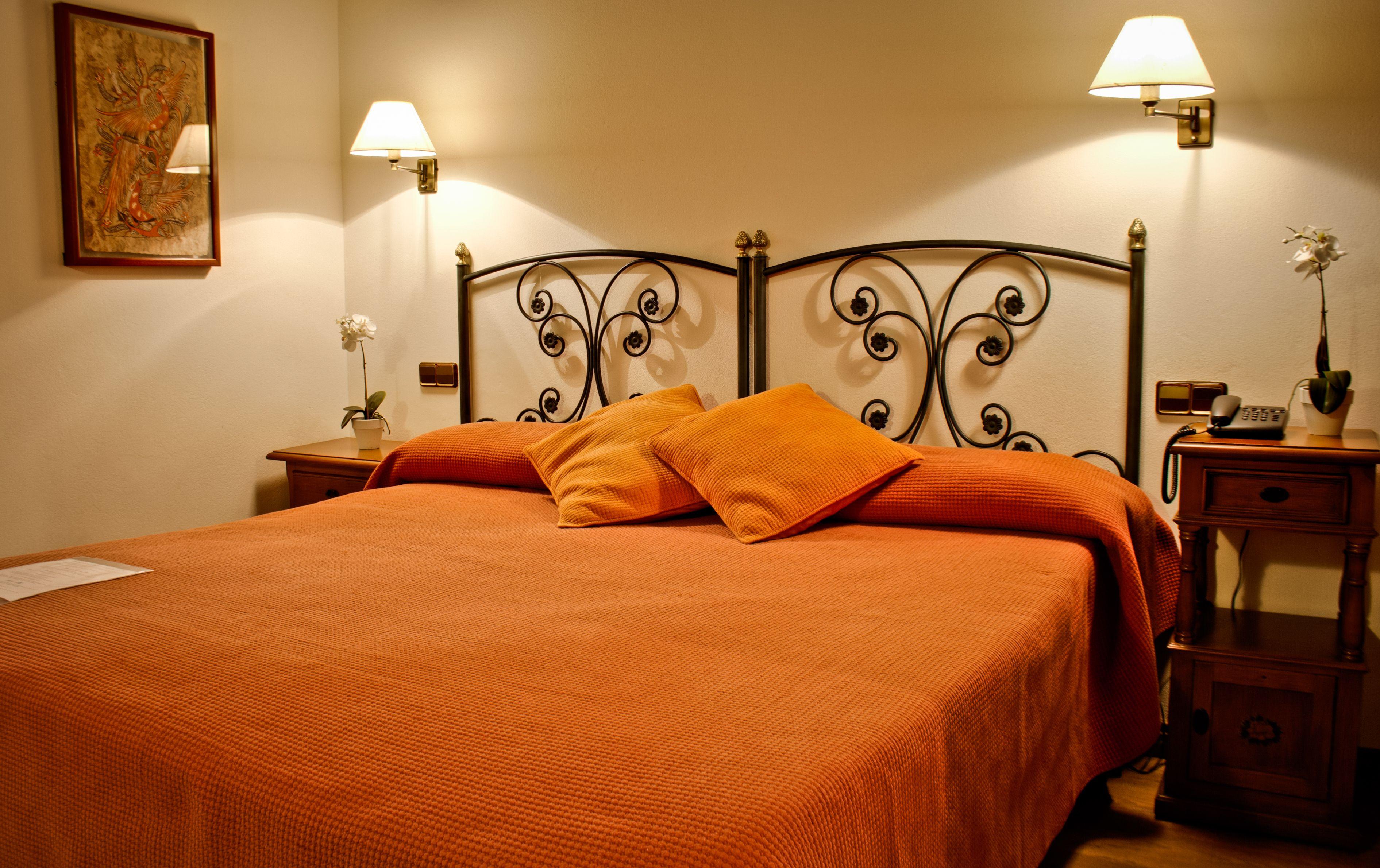 Habitaci n con cama matrimonial y cabeceros en forja negra for Mesillas de habitacion