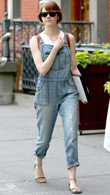 9ca5a6c47524f Emma Stone wearing lightly-washed denim overalls with a sleeveless top and  ankle-strap flat sandals.