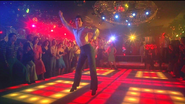 John Travolta como Tony Manero robándose el show en la pista de ...