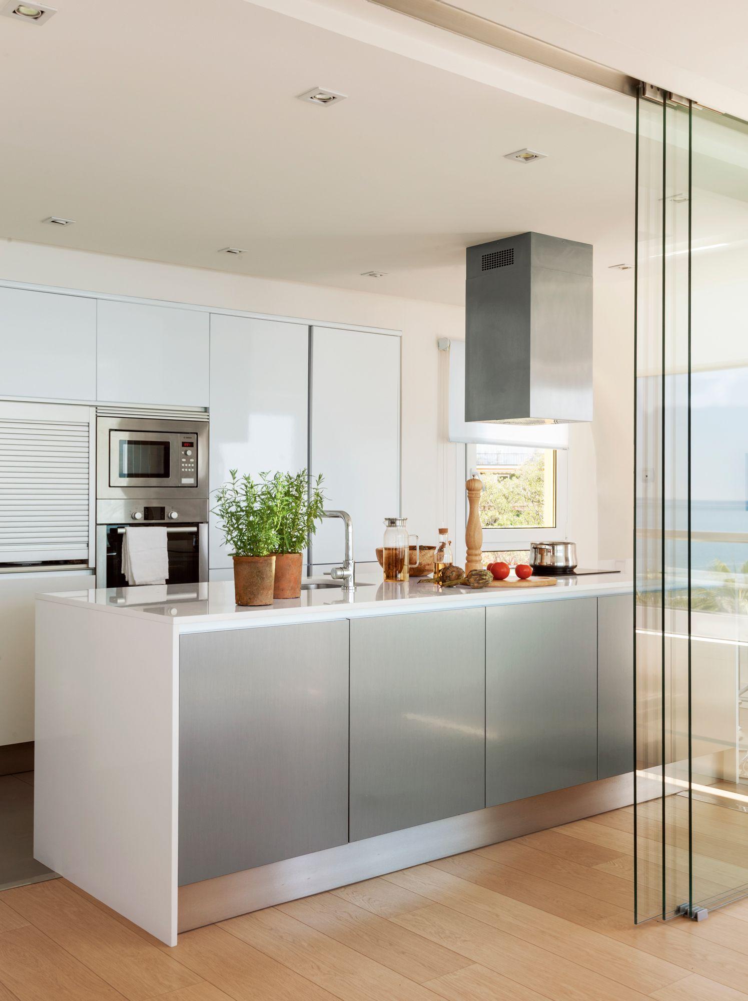 Cocina con isla central y puerta corredera de cristal con perfilería ...