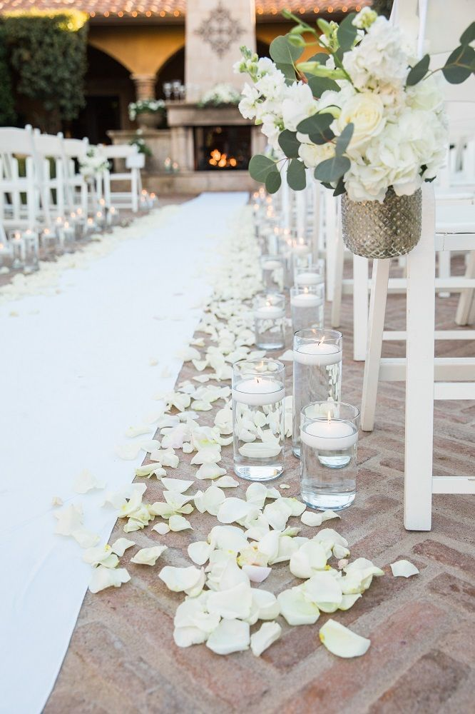 We couldn't ask for a more elegant aisle! Complete with white runner and ivory petals, and floral aisle markers and floating candles, this was a very romantic setting for a beautiful outdoor wedding ceremony. | Villa Siena | Robert Godridge Photography | #Villasiena #weddingvenue #gilbertarizona #arizonaweddings #arizonaweddingvenue #outdoorceremonyideas #ceremonydecor #aisledecor #whitecandleswedding