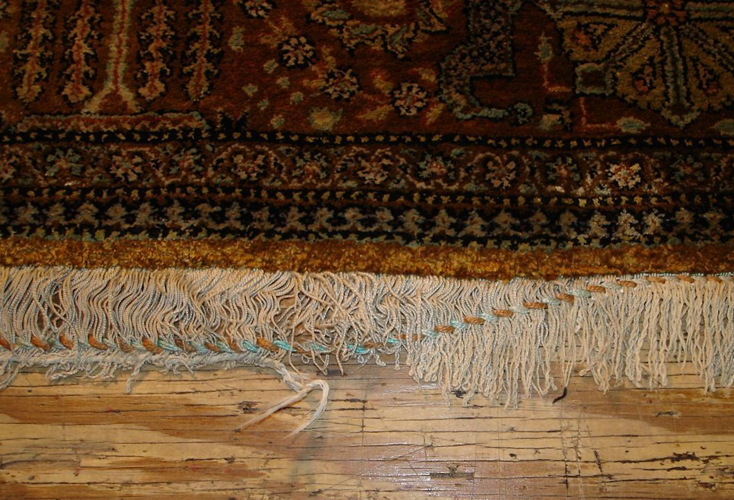 This picture shows a silk rug with the chain stitch slipping out of the end of the rug.  This becomes a open highway for the silk to fall out the end of the rug. #orientalrugrepair #rugrepair #herizpatchedcorner #rugrestoration #persianrugrepair #rugreweaving #orientalrugrestoration